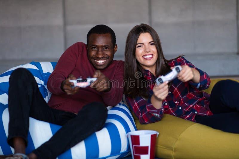 年轻人在家结合一起打电子游戏 库存照片