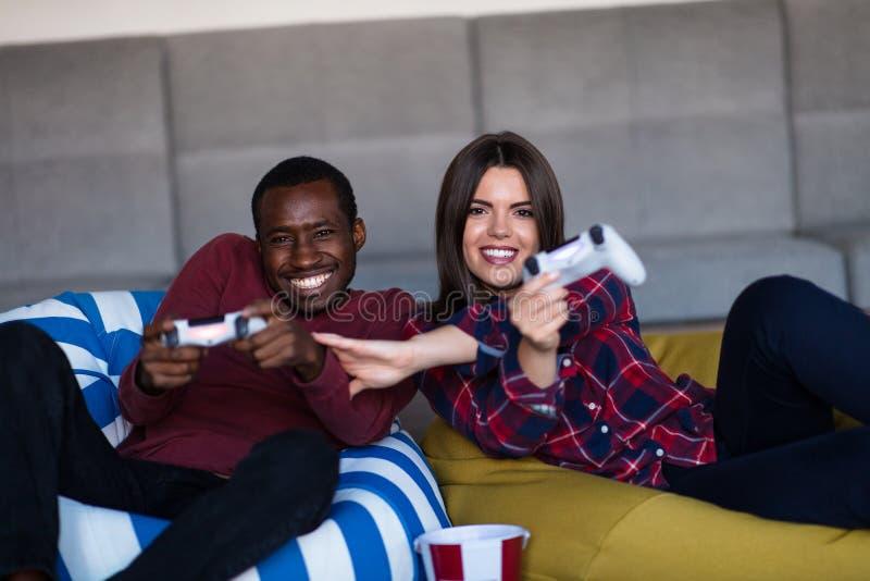 年轻人在家结合一起打电子游戏 免版税库存图片