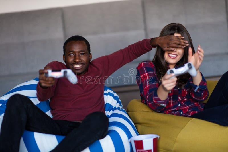 年轻人在家结合一起打电子游戏 免版税图库摄影