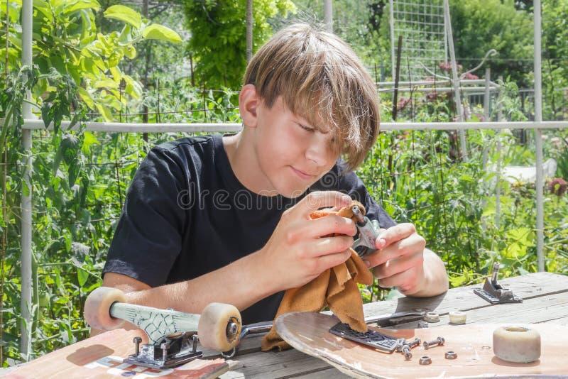 年轻人在庭院里修理在一个滑板的轮子在一个木摊位 库存照片