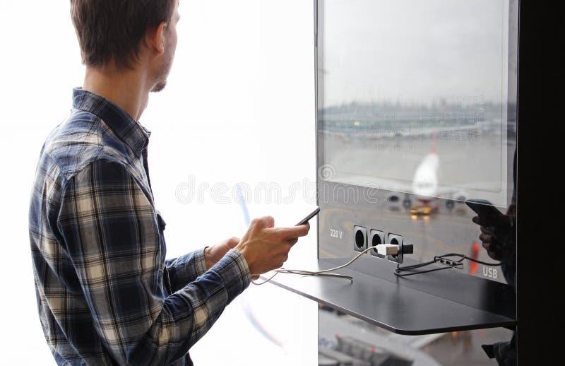 年轻人在机场终端充电一个智能手机 使用设备在旅途上 公开充电器服务 免版税库存图片