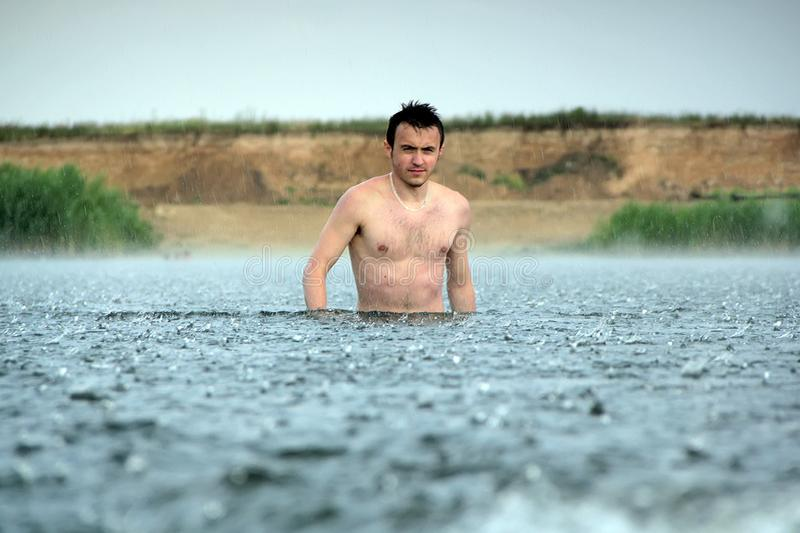 年轻人在河在雨下 免版税库存照片