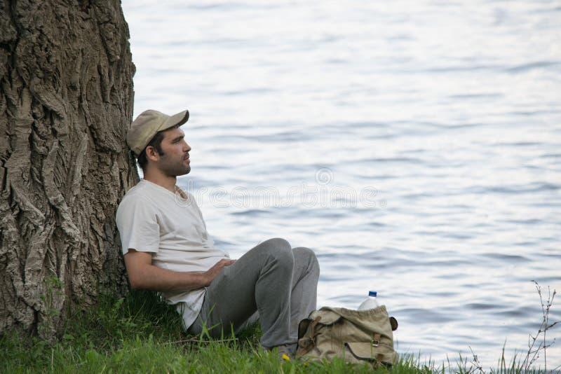 年轻人在河岸的一棵树附近休息 免版税库存照片