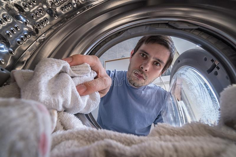 年轻人在洗衣机装载洗衣店 从里边看法 图库摄影