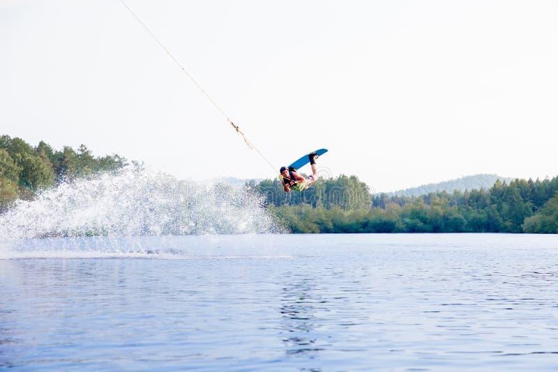 年轻人在湖的骑马wakeboard 库存图片
