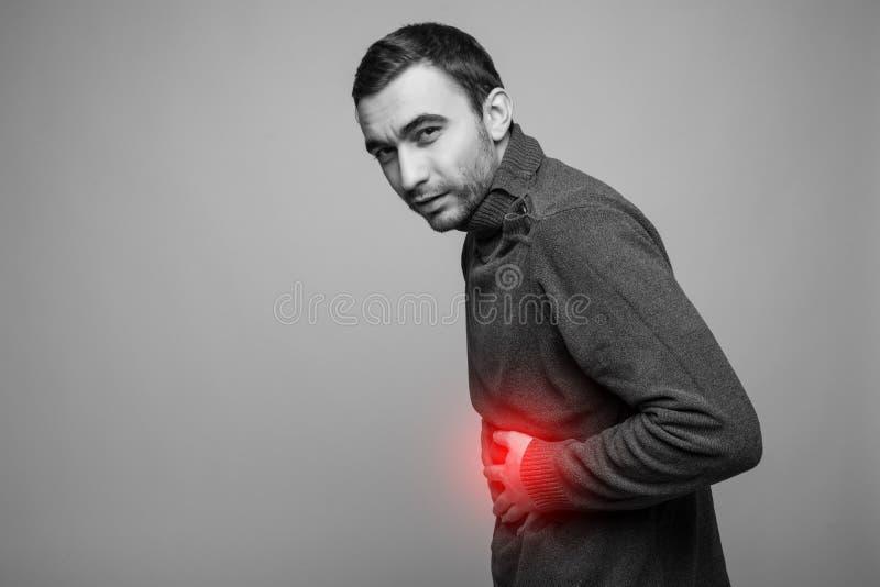 年轻人在痛苦中的握他病的胃,隔绝在灰色背景,与红色的单色照片作为硬化的一个标志 免版税图库摄影