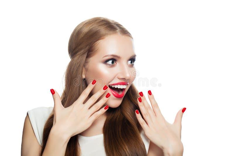 年轻人在白色背景隔绝的惊奇的妇女 有构成、健康头发和红色修指甲的笑的女孩 库存照片