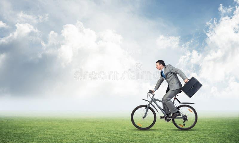 年轻人在绿草的骑马自行车 库存照片