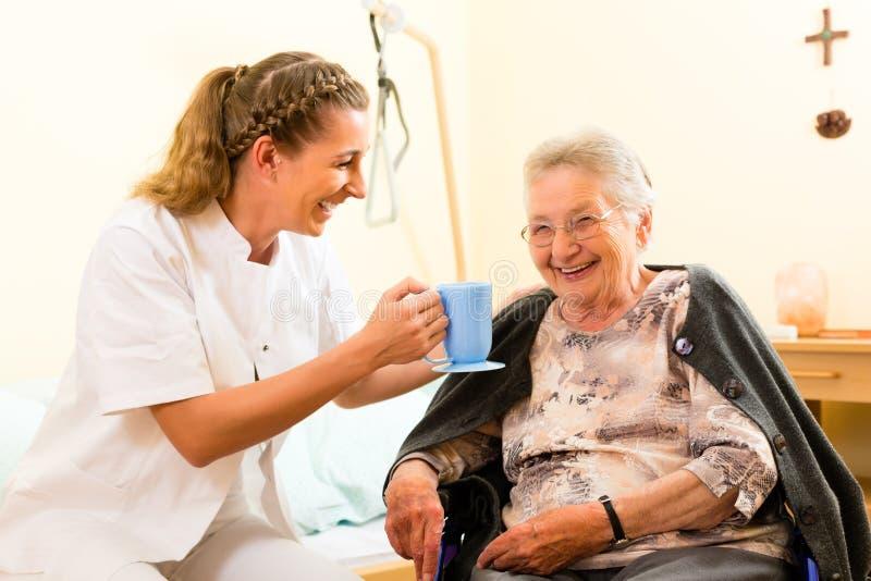 年轻人在老人院护理和女性前辈 免版税库存图片