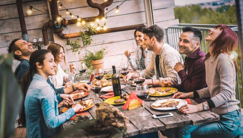 年轻人在阳台屋顶晚宴上一起享用和享用红葡萄酒,快乐的朋友们在餐厅享用烧烤美食 免版税库存照片