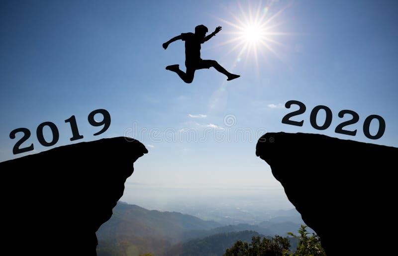 年轻人在2019年和2020年之间跳在太阳和通过在小山剪影晚上五颜六色的天空空白  库存照片