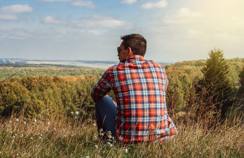 年轻人坐享受风景的小山 旅行和自由的概念 库存照片