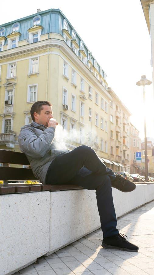 年轻人坐抽在街道的长凳一根电子香烟 Vape 免版税库存图片