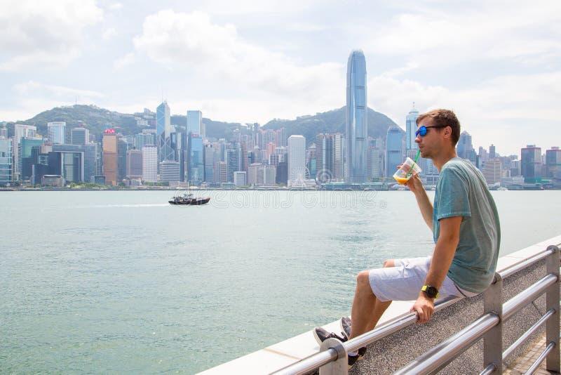 年轻人坐海岸线在香港 免版税库存图片