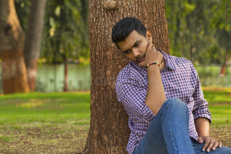 年轻人坐的和想法的倾斜反对树 免版税库存图片