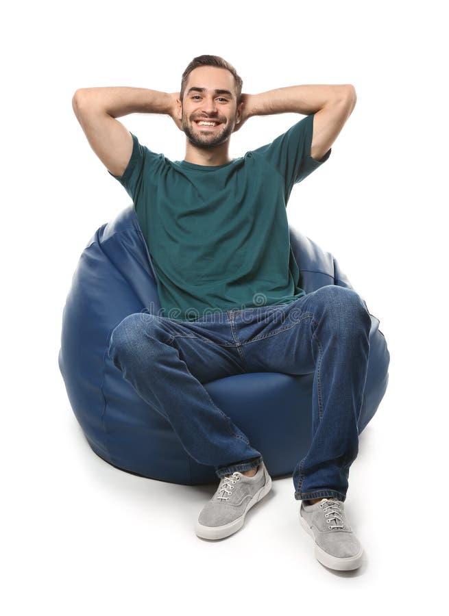 年轻人坐装豆子小布袋椅子反对白色背景 图库摄影