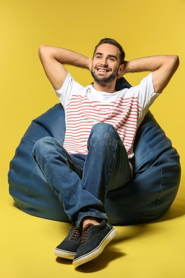 年轻人坐装豆子小布袋椅子反对颜色背景 免版税库存图片