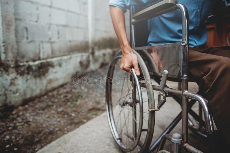 年轻人坐轮椅,室外残疾的概念 免版税库存图片