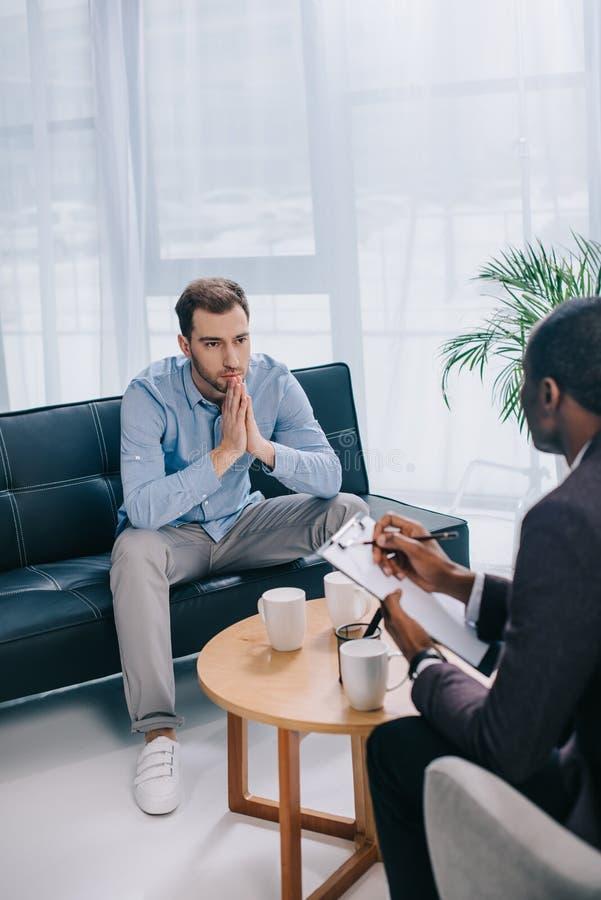 年轻人坐长沙发和谈话与非洲人 免版税库存图片