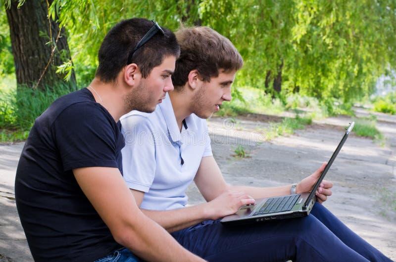 年轻人坐陆运使用膝上型计算机 免版税图库摄影
