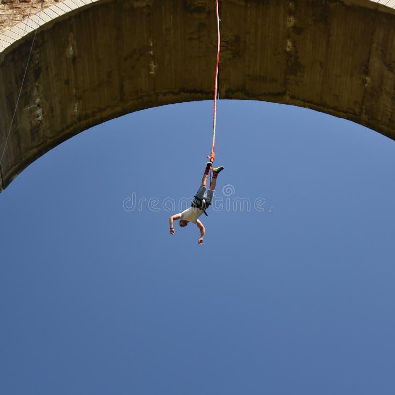年轻人垂悬在绳子的橡皮筋套头衫 库存图片