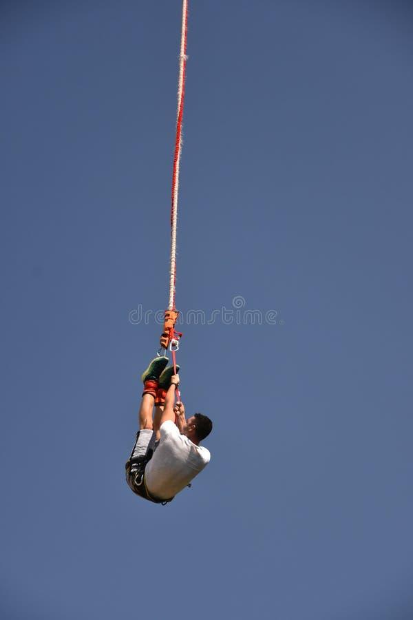 年轻人垂悬在绳子的橡皮筋套头衫 免版税图库摄影