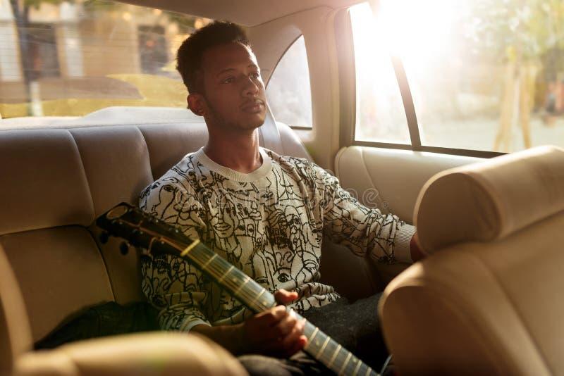 年轻人多种族坐在汽车的后座 拿着吉他的歌手,当旅行里面出租汽车时 免版税库存图片