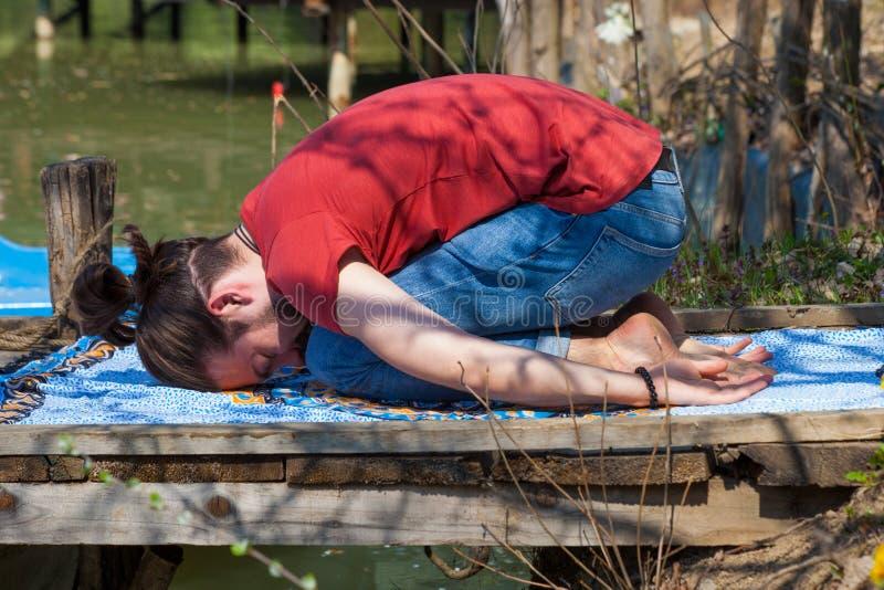 年轻人实践瑜伽由湖儿童姿势的夏日放松和休息的 免版税图库摄影