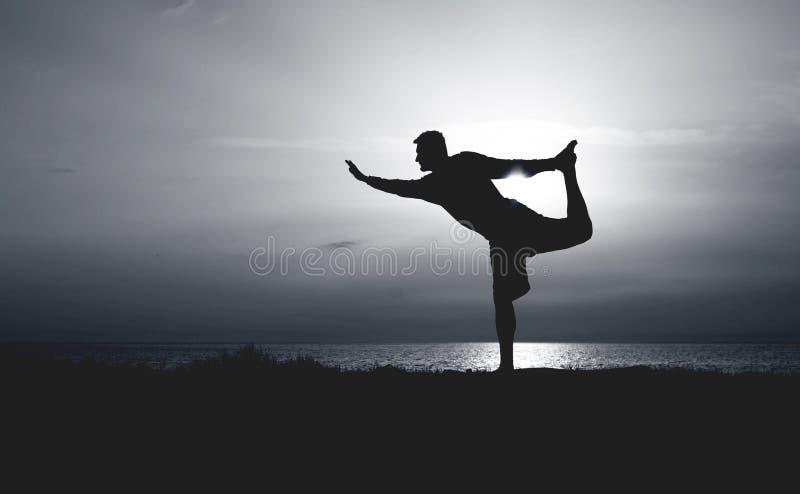 年轻人实践的瑜伽剪影  在海岸身分弓姿势的日落 免版税图库摄影