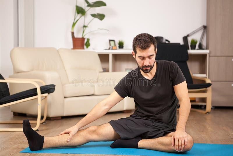 年轻人实践的瑜伽在他的客厅 免版税库存图片