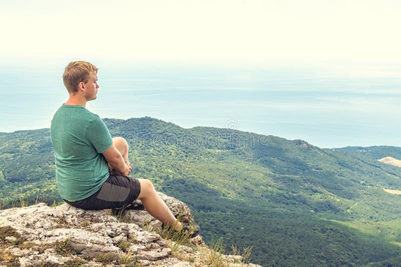 年轻人实践的瑜伽姿势坐岩石峰顶 人做凝思和享用视图 库存照片