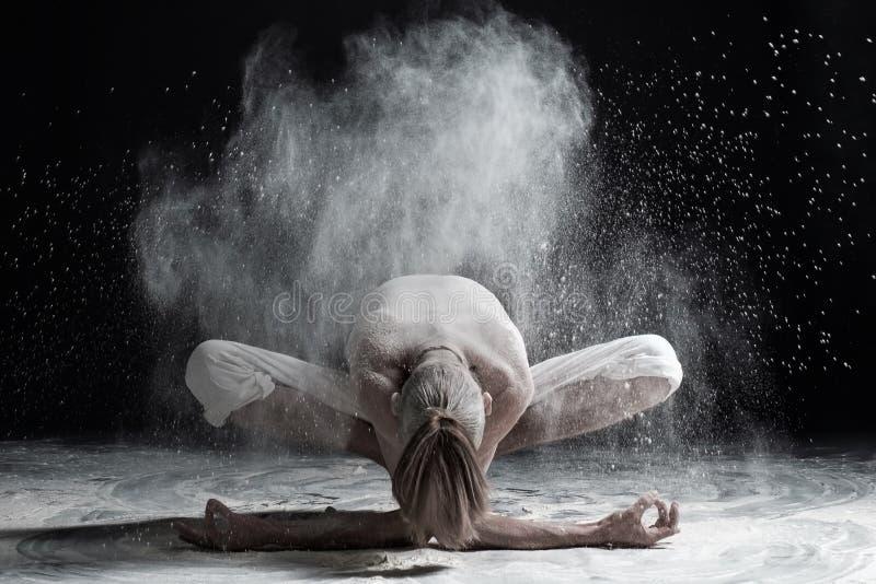 年轻人实践的瑜伽,坐在与向前弯的诗歌选锻炼, Malasana姿势的变异 库存照片