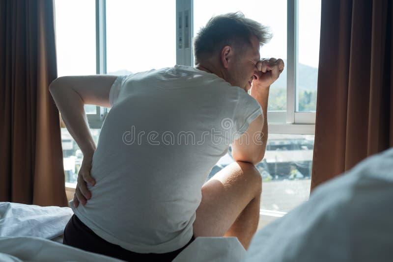 年轻人室内坐在他的床感觉疼痛  免版税库存图片
