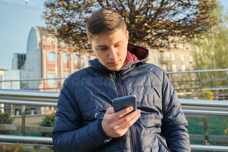 年轻人室外画象20岁,与无线耳机的学生听的音乐,读文本在智能手机 ?? 免版税图库摄影