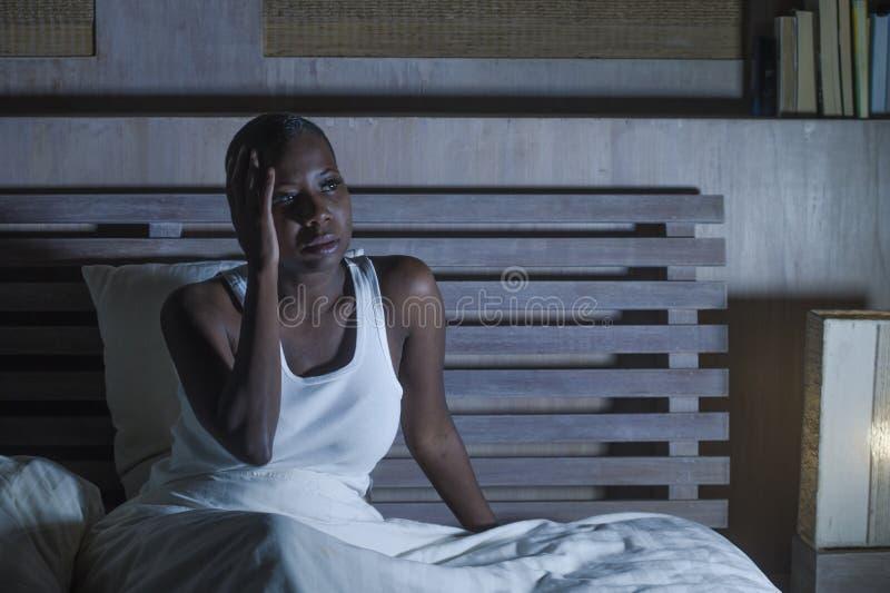 年轻人害怕的和在床生气无法压下的被注重的黑人非裔美国人的妇女睡觉遭受的宿酒头疼感觉 库存照片