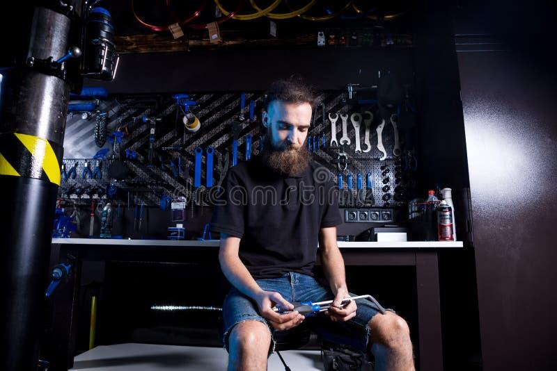 年轻人小企业主画象有胡子的 人自行车技工坐与工具的车间工作者在他的手上在a 库存图片