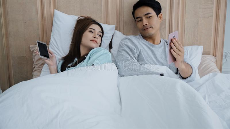 年轻人已婚夫妇使用了聊天在床上的智能手机 免版税图库摄影