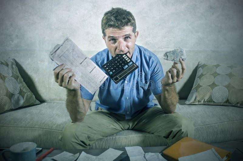 年轻人强调了并且淹没了银行人尖酸的计算器藏品混乱并且开收据文书工作绝望计算的月度exp 免版税库存照片