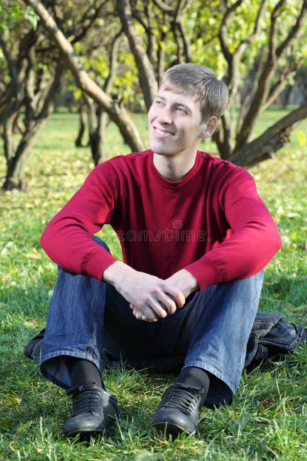 年轻人微笑并且坐草在公园 免版税图库摄影