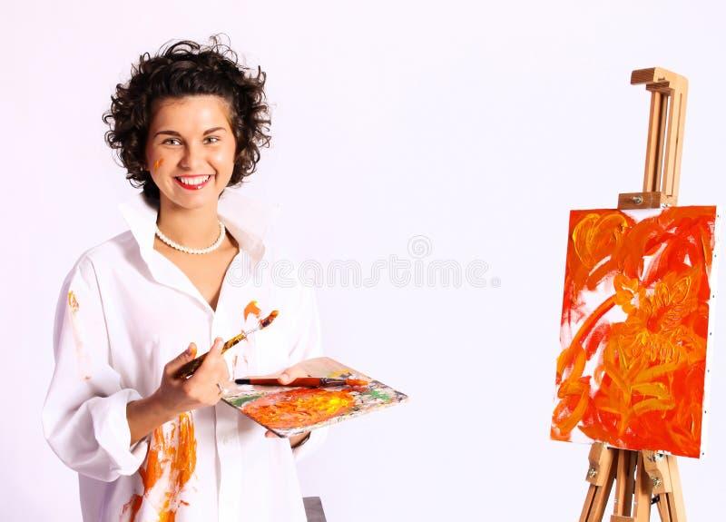 年轻人微笑的卷曲妇女画家 库存照片