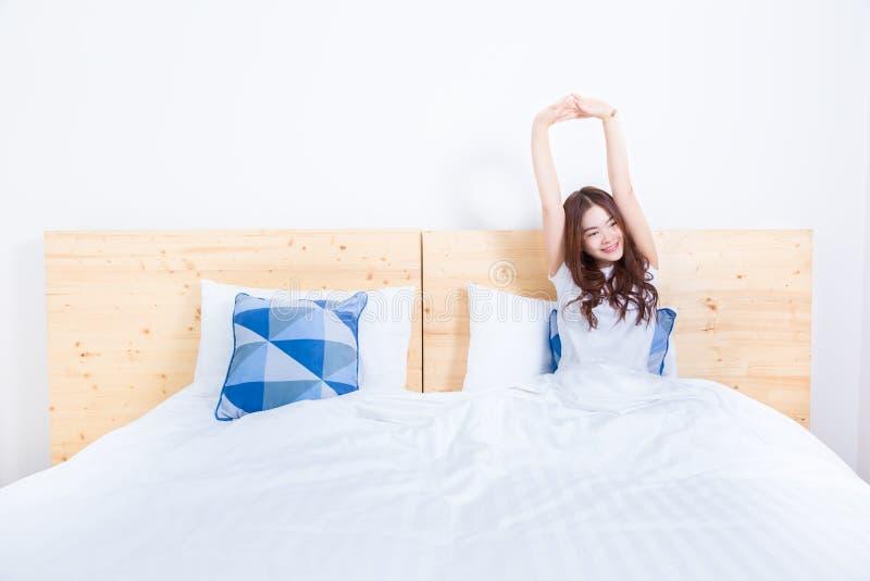年轻人微笑的愉快亚洲妇女醒,舒展,在她的wh 免版税库存照片