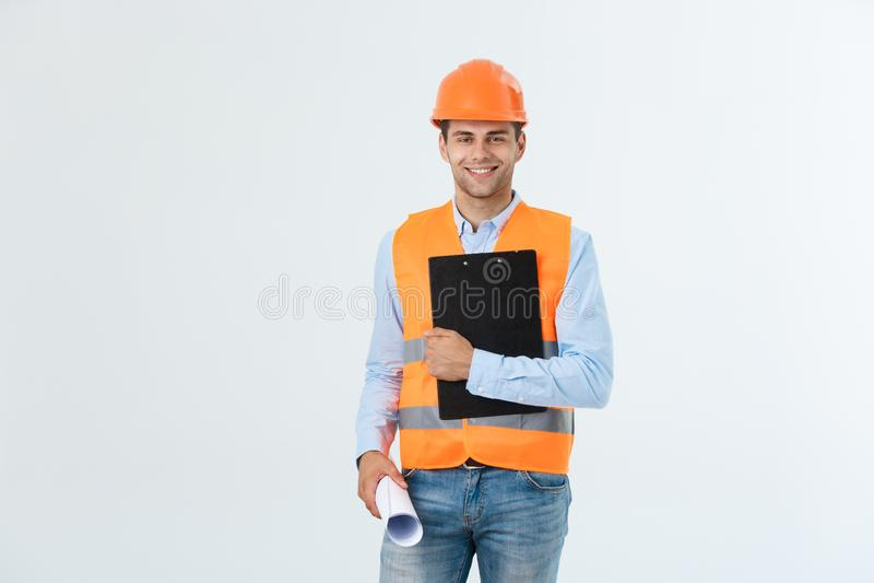 年轻人微笑的英俊的建筑师工程师半身画象摆在与图纸的橙色盔甲的看 免版税库存照片