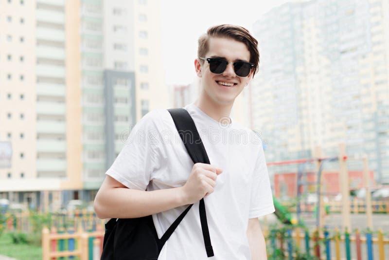 年轻人微笑秘密审议与背包的 室外样式 库存照片