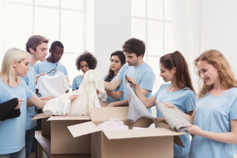 年轻人志愿小组与衣物捐赠一起使用 免版税图库摄影