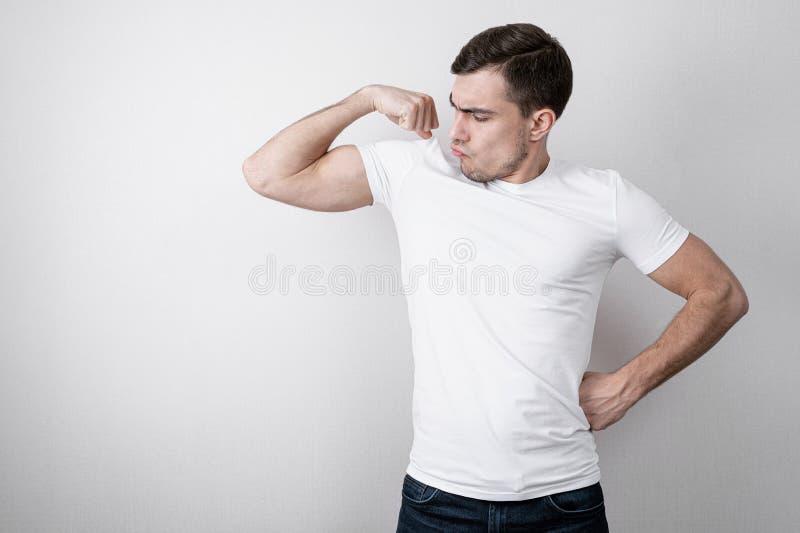 年轻人快乐的画象白色空白的T恤杉的显示他的在灰色背景的手的二头肌与拷贝空间 免版税库存照片