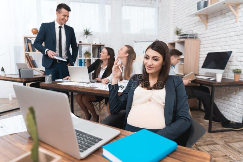 年轻人怀孕的女孩在有同事的办公室工作 怀孕的女实业家在办公室 免版税图库摄影