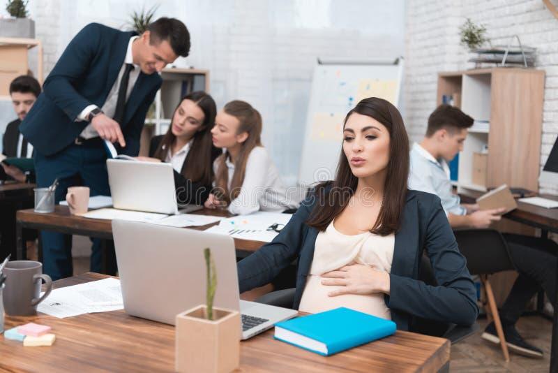 年轻人怀孕的女孩在有同事的办公室工作 怀孕的女实业家在办公室 库存图片