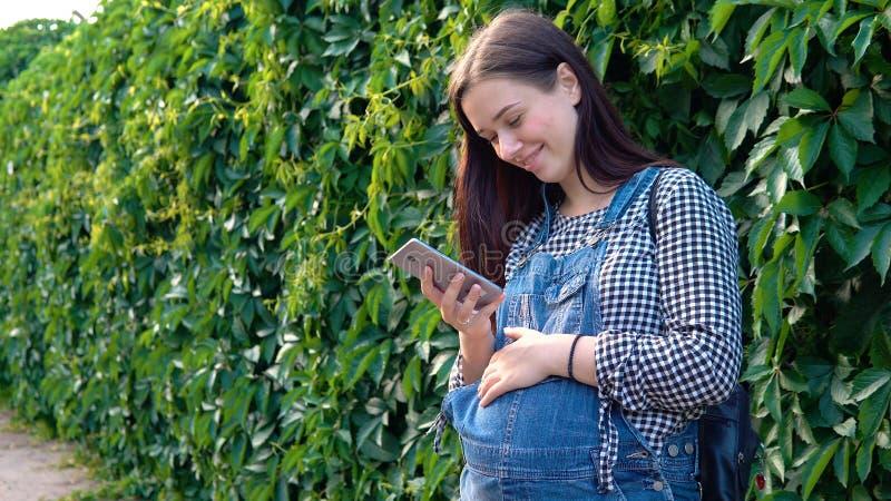 年轻人怀孕的女孩在看电话,在绿色背景的总体穿戴了 图库摄影