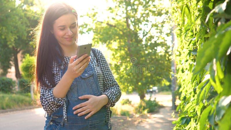 年轻人怀孕的女孩在看电话,在绿色背景的总体穿戴了 免版税库存图片