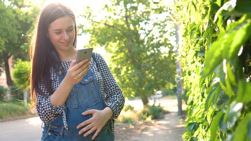 年轻人怀孕的女孩在看电话,在绿色背景的总体穿戴了 免版税库存照片